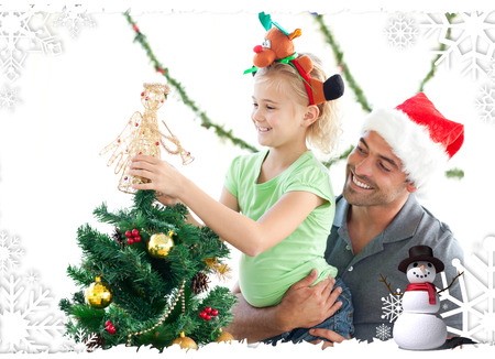 Cute little girl decorating the christmas tree with her father against christmas themed frame photo