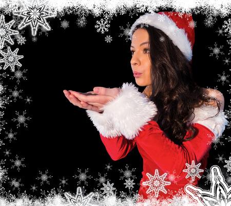 pere noel sexy: Jolie brunette � santa costume soufflant sur ses mains contre des flocons de neige Banque d'images