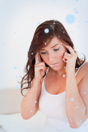Attractive brunette woman having a headache while sitting against snow falling photo
