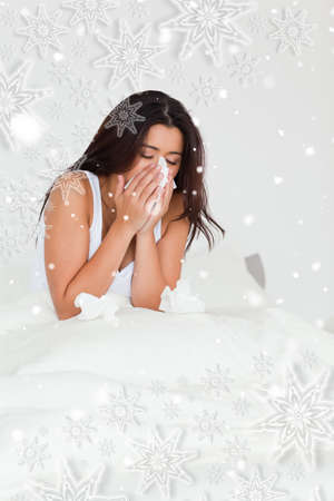 afflict: Brunette woman having a cold sitting in bed against snowflakes
