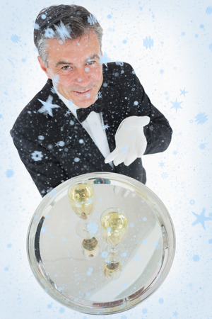 Waiter offering tray with glasses of champagne against snow falling photo