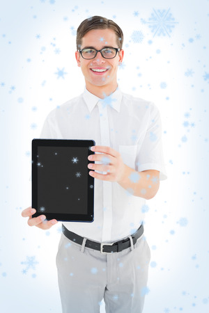 Geeky businessman showing his tablet pc against snow falling photo
