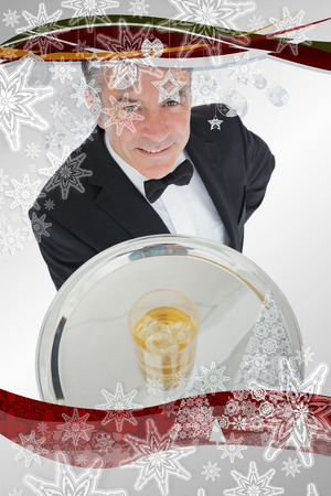 Waiter serving glass of whiskey on a tray against christmas frame photo