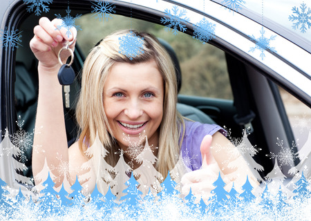 Charming female driver showing a key after bying a new car  against snowflakes and fir trees photo