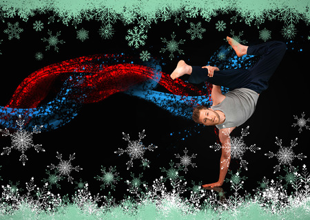 snow break: Break dancer showing his agility and balance against snow flake frame in green Stock Photo