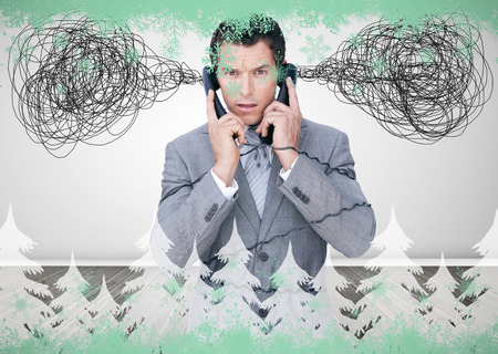 jumbled: Overworked businessman holding two telephones against green snowflake design