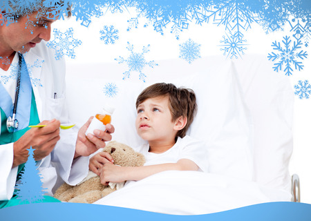 Happy little boy taking cough medicine  against snow flake frame in blue photo
