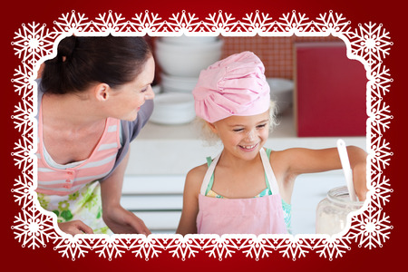 Cheerful mother and her daughter baking in a kitchen against snowflake frame photo