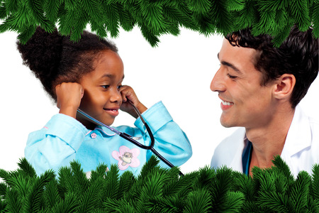 Smiling doctor and his patient playing with a stethoscope against fir tree branches forming frame photo