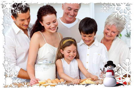 Parents and granparents looking at children baking against christmas themed frame photo