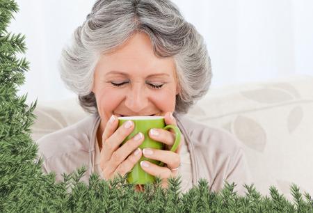 Senior drinking a cup of tea against green fir branches photo