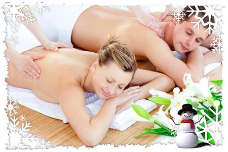 Loving young couple enjoying a back massage against christmas themed frame photo