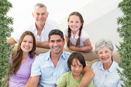 Composite image of smiling multigeneration family against green fir branches photo