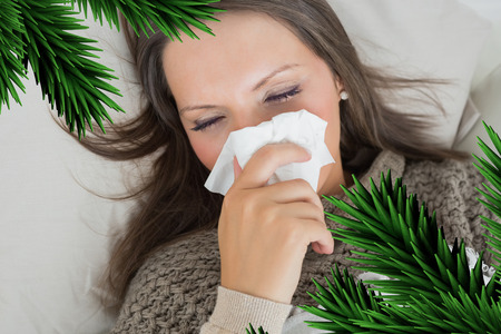 Sick woman lying on sofa and blowing nose against digitally generated fir tree branches photo