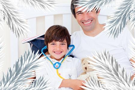 Cheerful father and his sick son playing with a stethoscope against fir tree branches forming frame photo