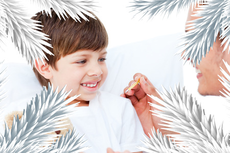Handsome doctor taking little boys temperature against fir tree branches forming frame photo