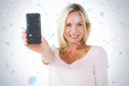 Happy blonde showing her smartphone against snow falling photo
