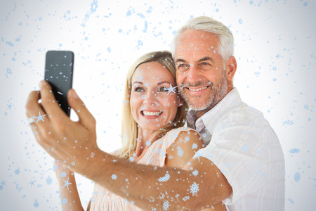Happy couple posing for a selfie against snow falling photo