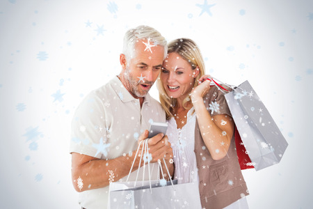 Happy couple holding shopping bags and smartphone against snow falling photo