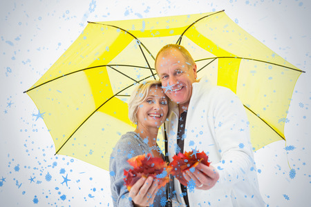 Happy mature couple showing autumn leaves under umbrella against snow falling photo