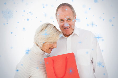 Older couple holding red gift bag against snow falling photo