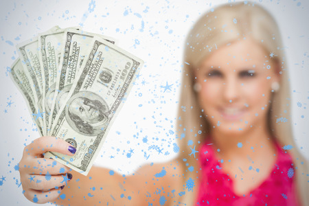 Beautiful blonde holding 100 dollars banknotes against snow falling photo