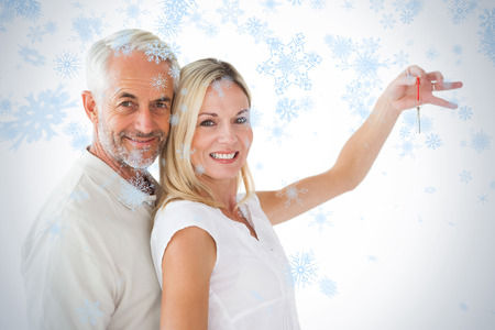 Happy couple showing their new house key against snow falling photo