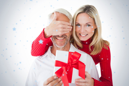 Smiling woman covering partners eyes and holding gift against snow falling photo