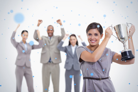 Woman holding up a cup with enthusiastic coworkers against snow falling photo