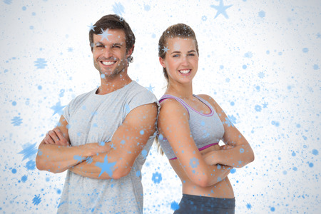 Portrait of a sporty young couple with arms crossed against snow falling photo