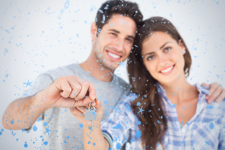 Man and wife holding a key with a house keychain against snow falling photo