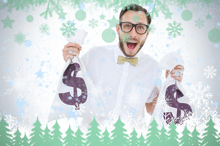 Geeky businessman holding money bags against snowflakes and fir trees in green photo