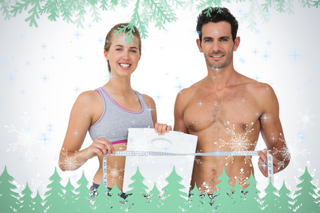 Sporty couple holding scales and measuring tape against frost and fir trees in green photo