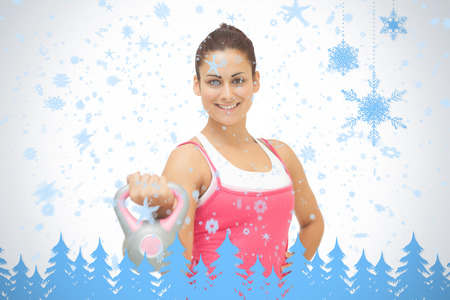 Cheerful sporty brunette holding grey and pink kettlebell against snowflakes and fir trees in blue photo