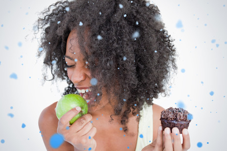Young woman going to eat a delicious green apple against snow falling photo