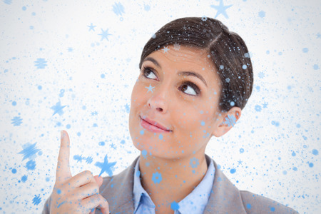Close up of female entrepreneur pointing and looking up against snow falling photo