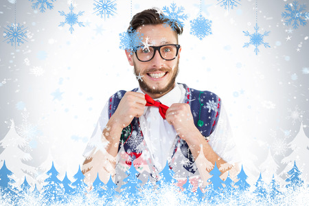 Geeky hipster wearing christmas vest against snowflakes and fir trees photo