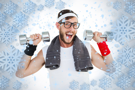 geeky: Geeky hipster lifting dumbbells in sportswear against snowflake frame