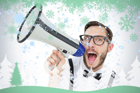 Geeky businessman shouting through megaphone against snowflakes and fir tree in green photo