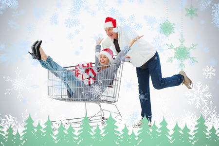 Festive mature couple in winter clothes with trolley and gifts against snowflakes and fir trees in green photo