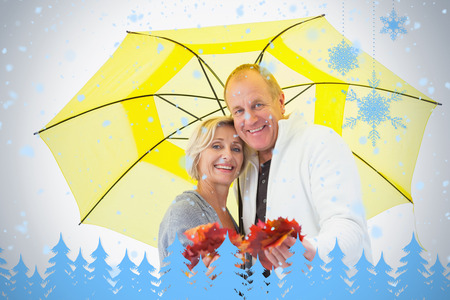 Happy mature couple showing autumn leaves under umbrella against snowflakes and fir trees in blue photo