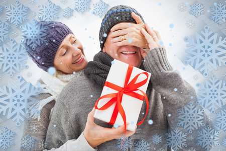 Happy mature woman hiding gift from partner against snowflake frame photo
