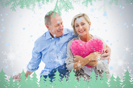 Happy mature couple with heart pillow against frost and fir trees in green photo