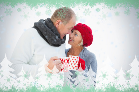 Happy mature couple in winter clothes holding mugs against green snowflake design photo