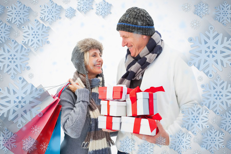 Mature couple in winter clothes holding gifts against snowflake frame photo