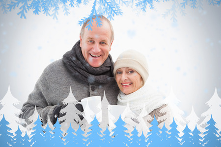 Happy mature couple in winter clothes holding mugs against frost and fir trees photo