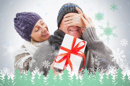 Happy mature woman hiding gift from partner against snowflakes and fir trees in green photo