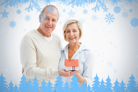 Happy mature couple with model house against snow flake frame in blue photo