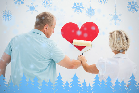 Happy older couple painting red heart against snowflakes and fir trees in blue photo