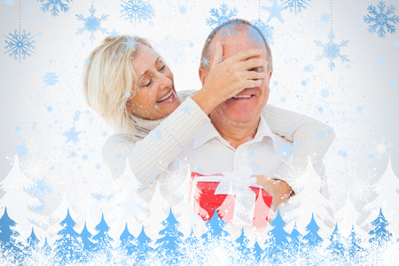 Older woman covering her partners eye while holding present against snowflakes and fir trees photo